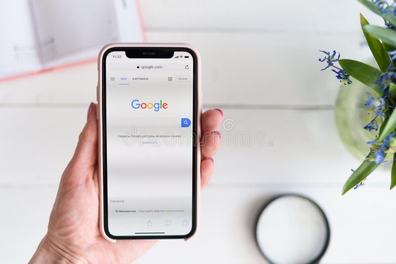 KHARKIV, ΟΥΚΡΑΝΙΑ - 10 Απριλίου 2019: Η γυναίκα κρατά το iPhone Χ της Apple με Google περιοχή COM στην οθόνη Σελίδα αναζήτησης στοκ εικόνες