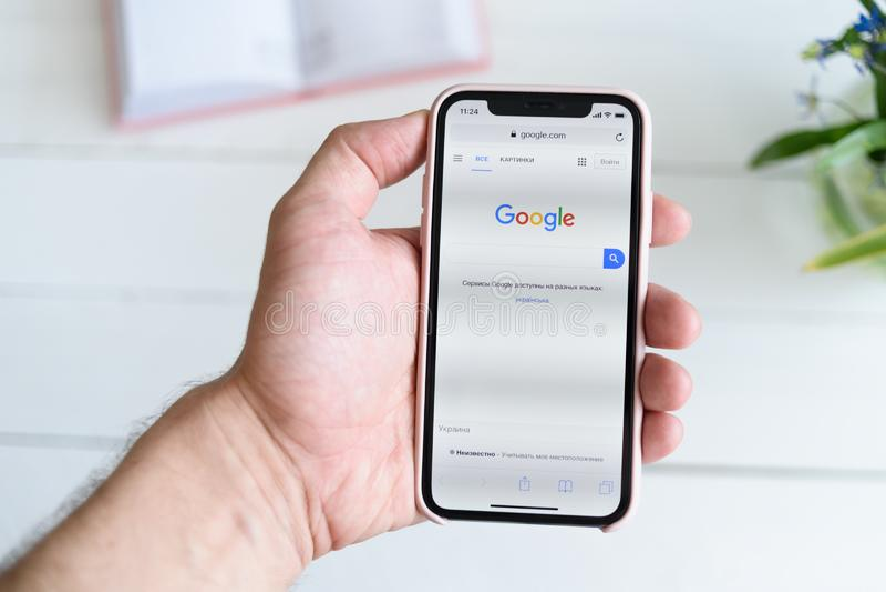 KHARKIV, ΟΥΚΡΑΝΙΑ - 10 Απριλίου 2019: Το άτομο κρατά το iPhone Χ της Apple με Google περιοχή COM στην οθόνη Σελίδα αναζήτησης στοκ φωτογραφία