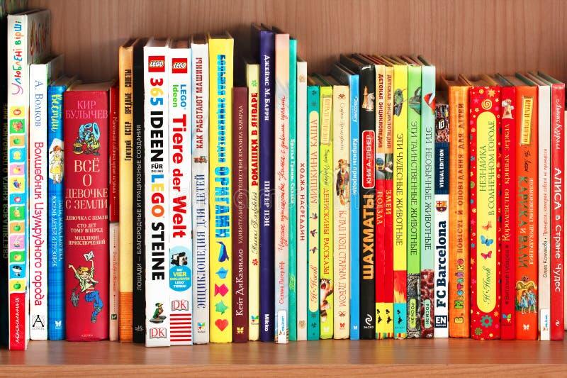 KHARKIV, de OEKRAÏNE - Januari vierentwintigste, 2019: Boekenplank met kinderenboeken in heldere kleurrijke dekking stock foto