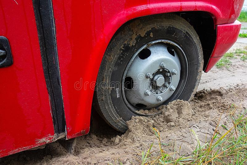 Kharkiv, Ucrânia, em agosto de 2019 roda do ônibus é atolado na areia Carro grande vermelho colado na lama Problema de tráfego na imagens de stock