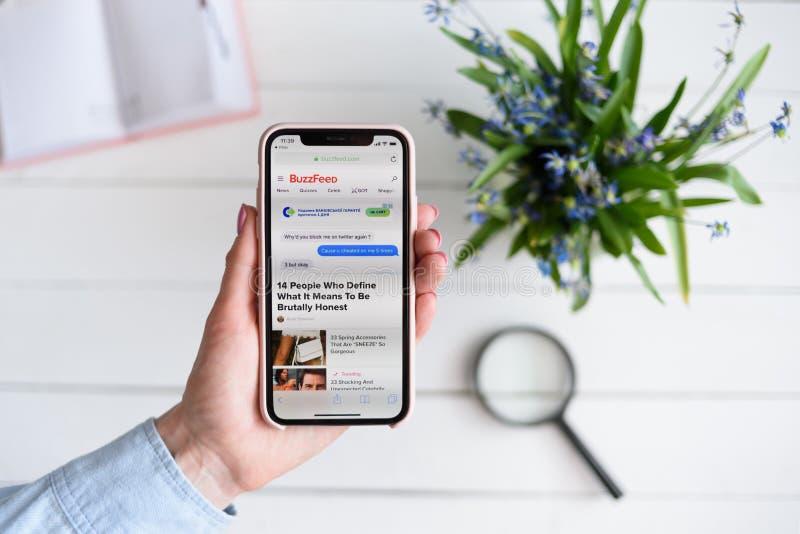 KHARKIV, UCRÂNIA - 10 de abril de 2019: A mulher guarda o iPhone X de Apple com BuzzFeed local de COM na tela P?gina da busca fotografia de stock royalty free
