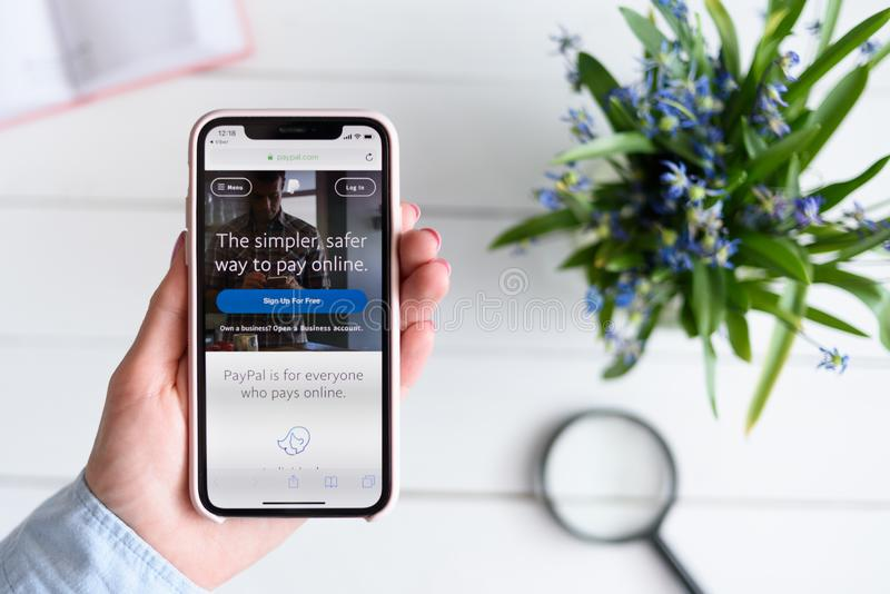 KHARKIV, UKRAINE - April 10, 2019: Apple iPhone X in female hand with paypal.com site on the screen.  stock image