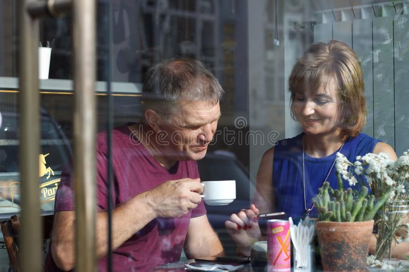 Elderly couple man and woman behind a cafe window on a date look at the phone, drink coffee and chat royalty free stock photos