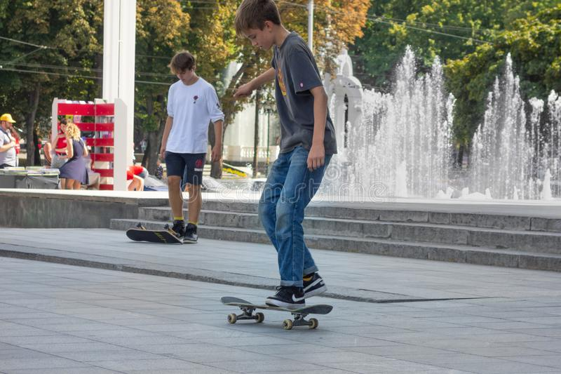 Kharkiv, Ukraine, August, 2019 Teenagers with skateboards in city landscape. Modern active lifestyle concept. Boy skater makes stock photos
