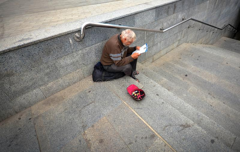 Kharkiv, Ukraine - August 19, 2019: Unidentified local homeless man sitting on the stairs and reading newspaper. royalty free stock images
