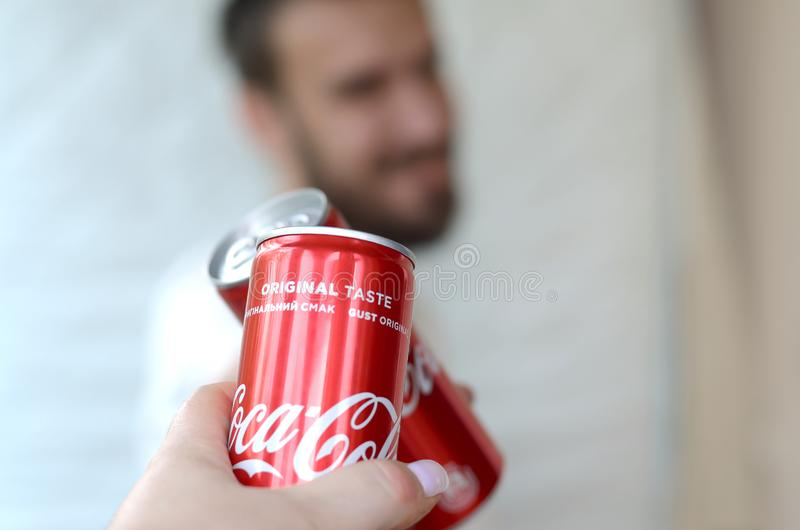 Happy young man raise Coca-Cola tin can with female friend in garage interior royalty free stock photo