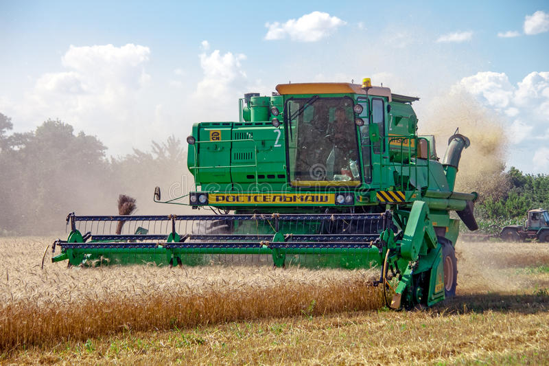KHARKIV, UKRAINE - JULY 12, 2011: Harvesting wheat field in Kharkiv Oblast in the Ukraine. Combine harvests wheat on a field in sunny summer day royalty free stock image