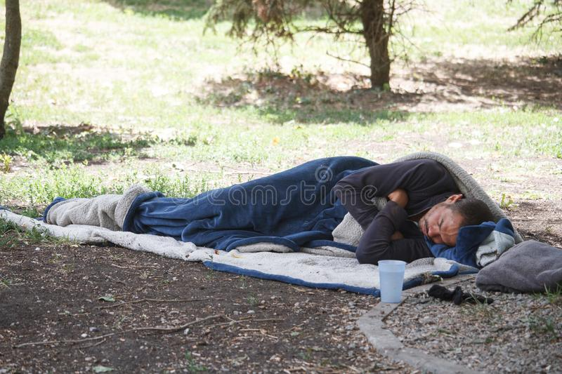 A lone tourist hid in a sleeping bag and sleeps on the ground in a city park, a homeless person sleeps in the afternoon in the stock photo