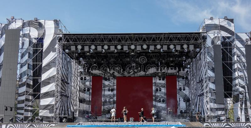 Kharkiv, Ukraine, Sept 2019 Music concert stage with light and sound equipment during performance or rehearsal under blue sky. Group of girls and technicians stock photo