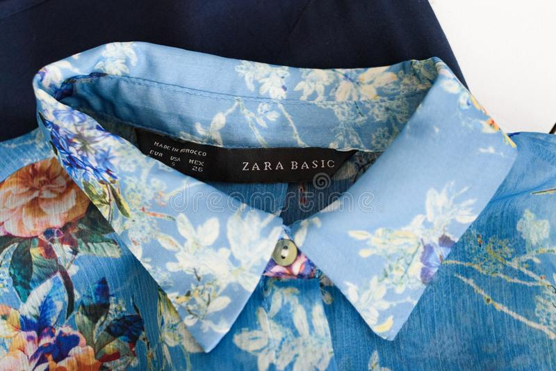 KHARKOV, UKRAINE - APRIL 27, 2019: Black label ZARA BASIC and collar of blue floral blouse. Clothes concept. Details royalty free stock photography