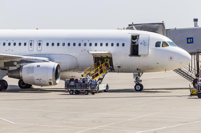 Kharkov/Ukraine - August 19, 2018: Airbus A319 of FANair in Kharkov Airport, baggage luggage loading.  royalty free stock photos