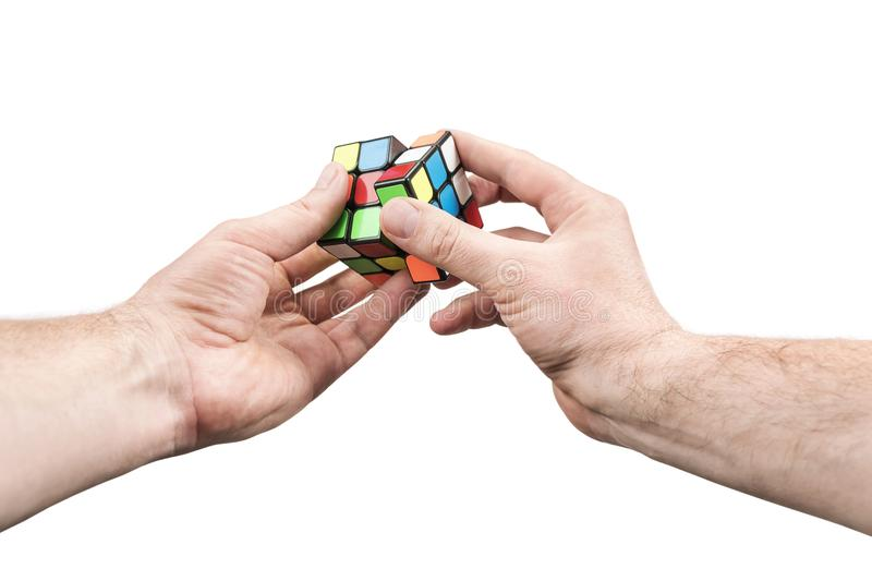 Kharkov, Ukraine - May 31, 2018: Hands twisting the Rubik cube. Kharkov, Ukraine - May 31, 2018: Male hand holding in his hand a Rubik`s cube and spin one of its royalty free stock images