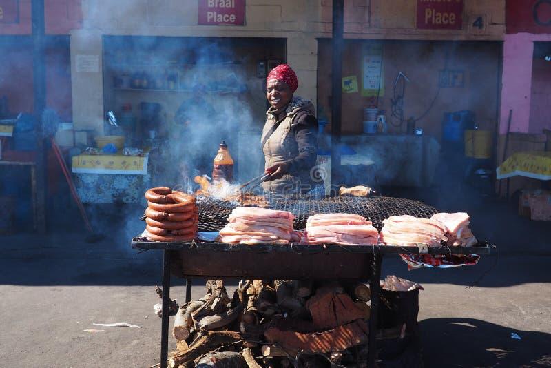 Khayelitsha Sydafrika - 29 Augusti 2018: Kvinna som lagar mat köttinaförsamlingen i Sydafrika royaltyfri bild