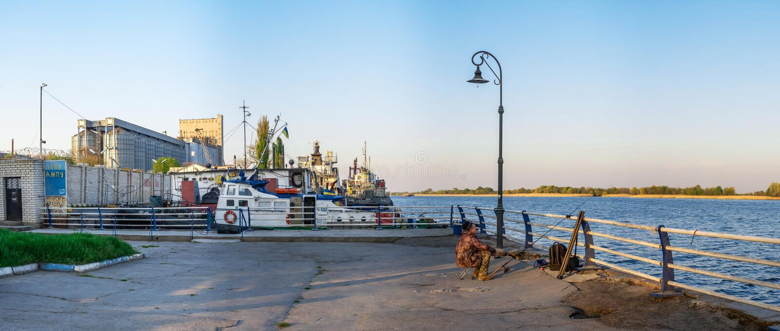 Fishermen on the waterfront in Kherson, Ukraine. Kherson, Ukraine - 04.27.2019. Fishermen on the embankment alley in Kherson, Ukraine, on a spring evening royalty free stock image