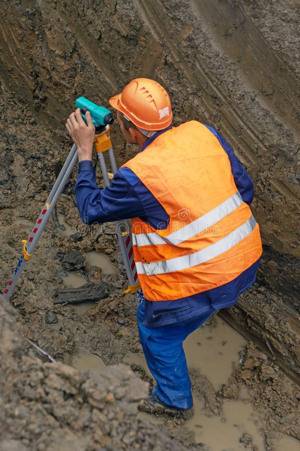 KHIMKI RYSSLAND - Juni 14, 2018: Inspektören utför den geodetiska granskningen för cadastren royaltyfri fotografi