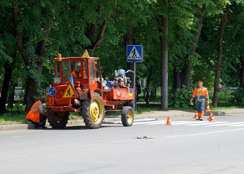 Khmelnitsky, de Oekraïne, 26 kan 2016: Arbeiders die een wegteken herstellen stock afbeeldingen