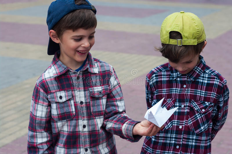 KHMELNITSKY, UKRAINE - JULY 29, 2017: Boy holds an origami pigeon in his hands. He shows origami to his twin brother. He is excited and happy royalty free stock images