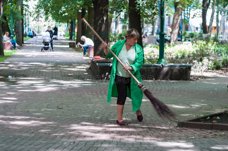KHMELNITSKY, UKRAINE - JULY 29, 2017: Sweeper in the park sweep stock photography