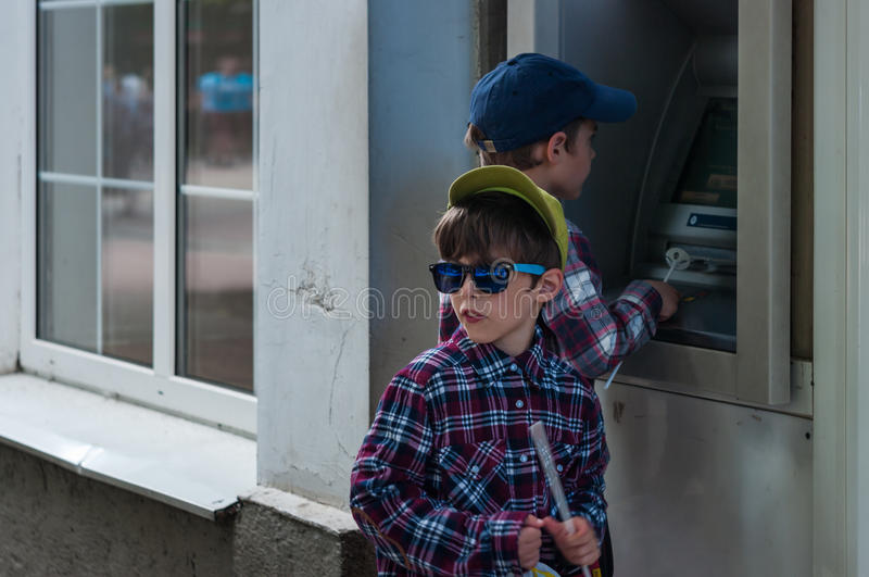 KHMELNITSKY, UKRAINE - JULY 29, 2017: Two brothers near the ATM. KHMELNITSKY, UKRAINE - JULY 29, 2017: The twin brothers play with the ATM royalty free stock photography