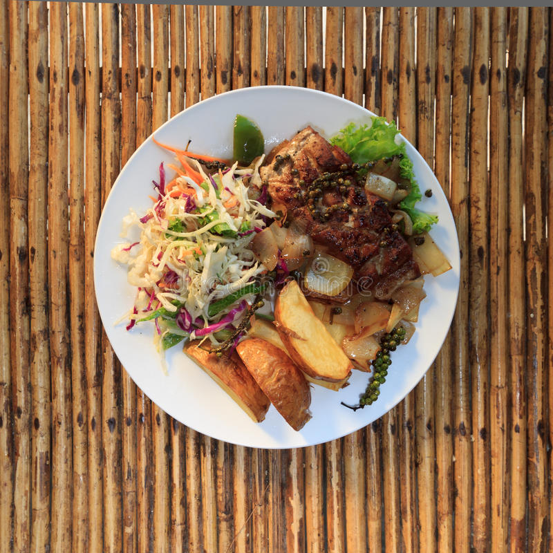 Khmer barracuda steak with vegetable salad royalty free stock photo