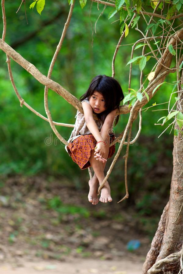Khmer Child in Cambodia. An unidentified Khmer Child plays in the jungle trees at the Temple Complex of Ta Prohm in Siem Reap Cambodia on April 1, 2011. The