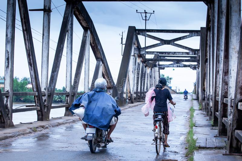 Khmer people riding motorcycles and bicycle across over the old French Bridge on rainy morning, Kampot, Cambodia. Khmer people riding motorcycles and bicycle royalty free stock images