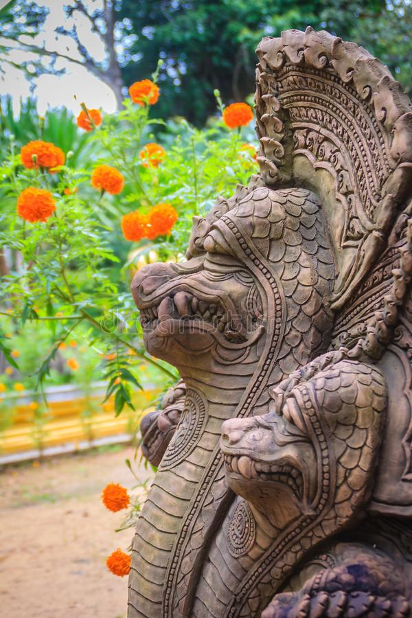 Khmer` s style Naga head made from sand stone at the public temple in Thailand. Naga or large snake according to Hindu belief. Khmer` s style Naga head made stock photo