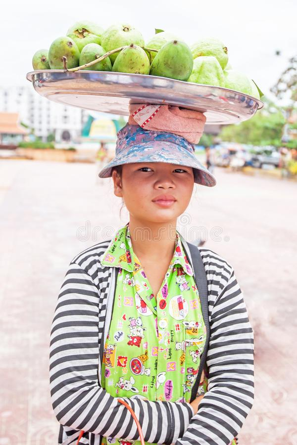 A Khmer young girl vendor carrying mangoes on the street at seaside stock images