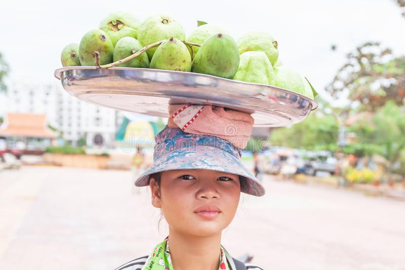 A Khmer young girl vendor carrying mangoes on the street at seaside royalty free stock photo