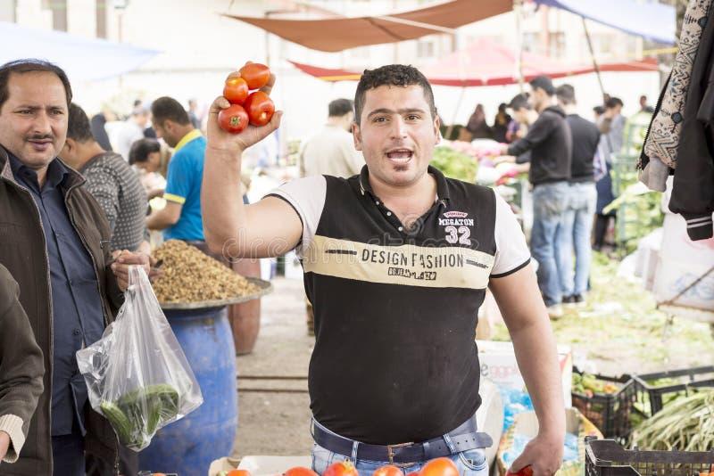 Khomam食用的年轻人的特写镜头画象的每日义卖市场蕃茄在手中 免版税库存照片