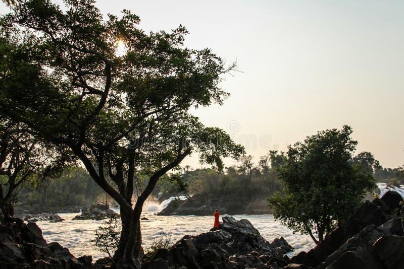 Khone Phapheng cai no pôr do sol com a monge que contempla o mekong, si Phan Don, província de Champasak, Laos imagem de stock royalty free