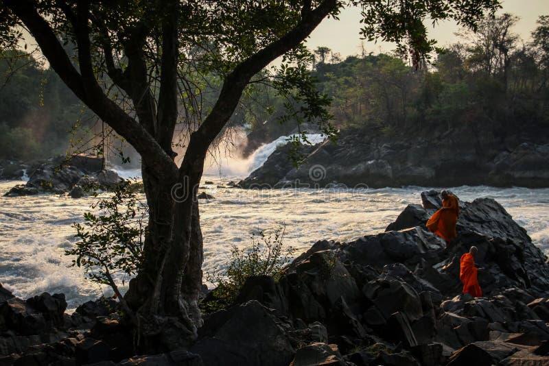 Khone Phapheng faller på solnedgången med buddistiska munkar som tycker om omgivningen, den siPhan universitetsläraren, det Champ royaltyfri bild