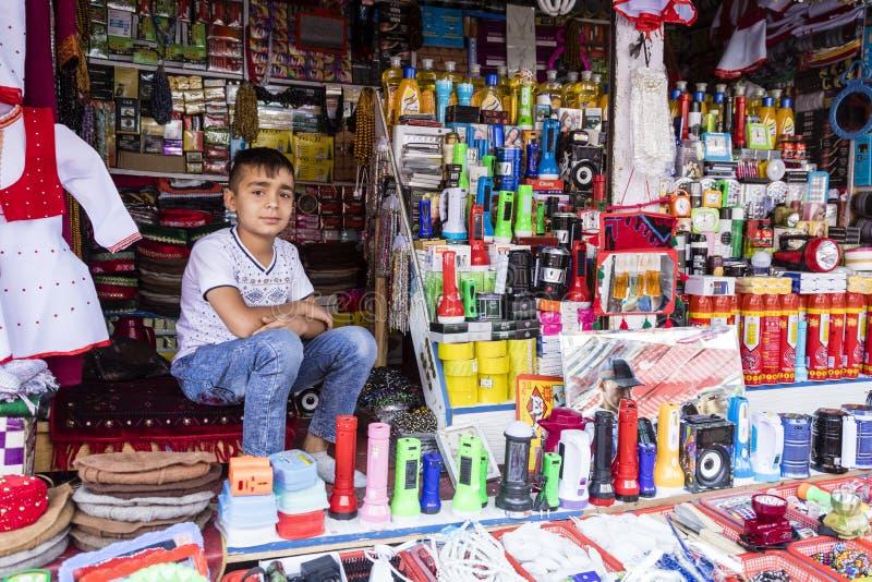 Khorog Tadzjikistan Augusti 25 2018: Den stiliga pojken sitter i hans stannar och att vänta på köparen av hans varor, Khorog, Tad royaltyfri fotografi