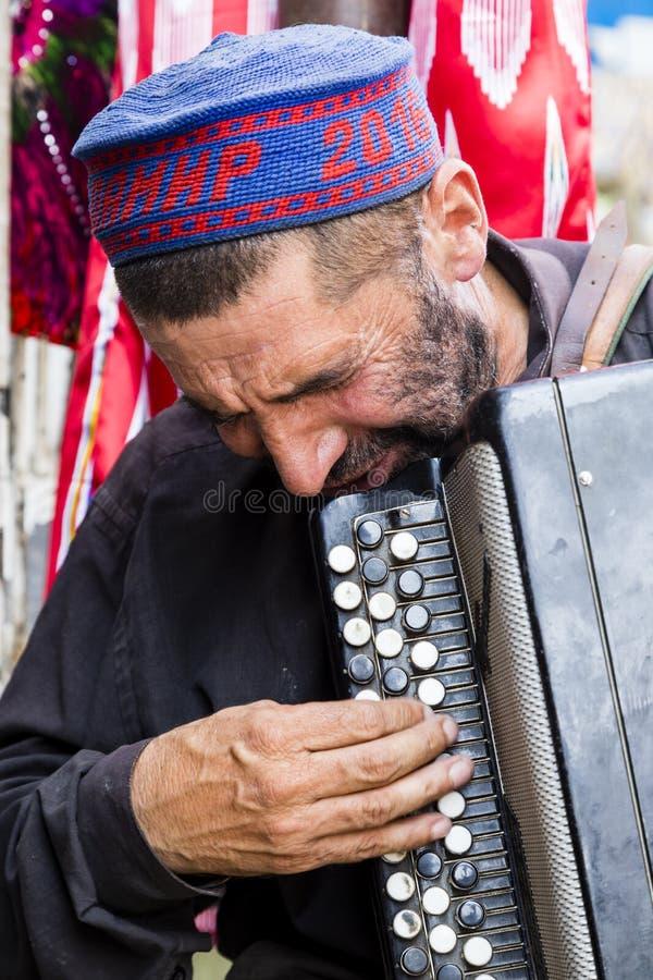 Khorog Tadzjikistan, Augusti 20 2018: En gammal musiker spelar på basaren i Khorog på hans dragspel royaltyfri fotografi