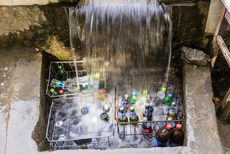 Khorog Tadzjikistan Augusti 25 2018: På vägrenen på den Pamir huvudvägen i Tadzjikistan kylas drinkar under en liten vattenfall royaltyfria foton