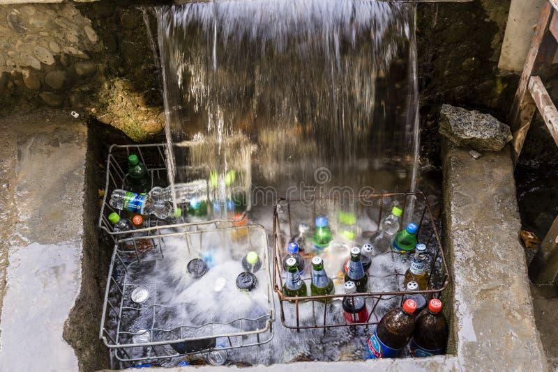 Khorog Tadzjikistan Augusti 25 2018: På vägrenen på den Pamir huvudvägen i Tadzjikistan kylas drinkar under en liten vattenfall fotografering för bildbyråer