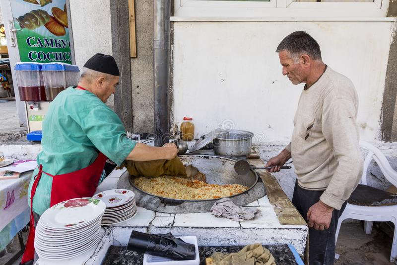 Khorog Tadzjikistan Augusti 25 2018: Två säljare lagar mat en rismaträtt i en stor pannkaka på marknaden i Khorog i Tadzjikistan arkivbild