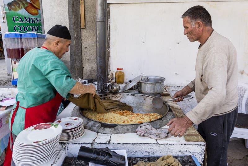 Khorog, Tagikistan 25 agosto 2018: Due venditori stanno cucinando un piatto del riso in un grande pancake al mercato in Khorog ne fotografia stock libera da diritti