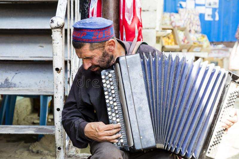 Khorog, Tajikistan, August 20 2018: An old musician plays on the bazaar in Khorog on his accordion royalty free stock image