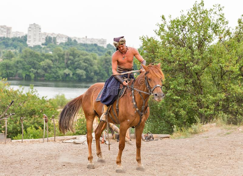 Ukrainian Cossack in Zaporozhian Sich. Khortytsia island, Ukraine. KHORTYTSIA, UKRAINE - JULY 03, 2018: Ukrainian Cossack horseman with bowl and arrow in royalty free stock photography