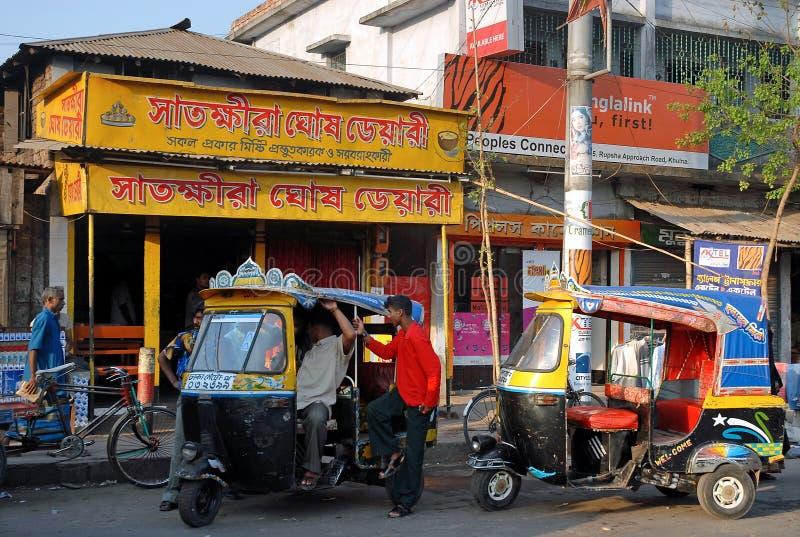 Khulna, Μπαγκλαντές: Δύο τρίτροχα ταξί με οδηγούς που περιμένουν επιβάτες σε ένα δρόμο στην Khulna στοκ φωτογραφίες