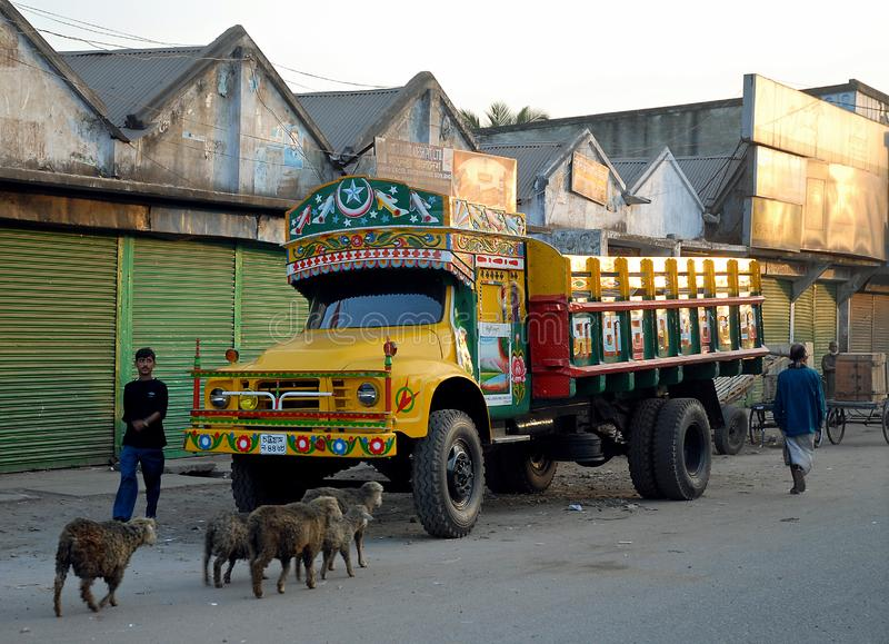 Khulna, Bangladesh:  A colorful truck parked on the street in Khulna. People and some sheep or goats walk past the truck. Local life scene in Khulna royalty free stock image