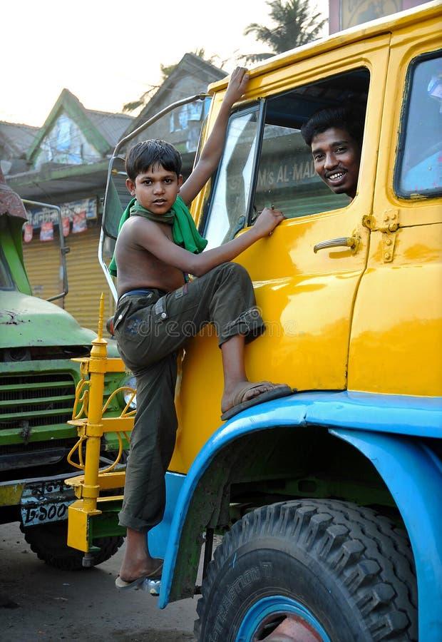 Khulna, Bangladesh: En ung pojke klättrar på hytten på en lastbil i Khulna med leende förare inne i arkivbilder