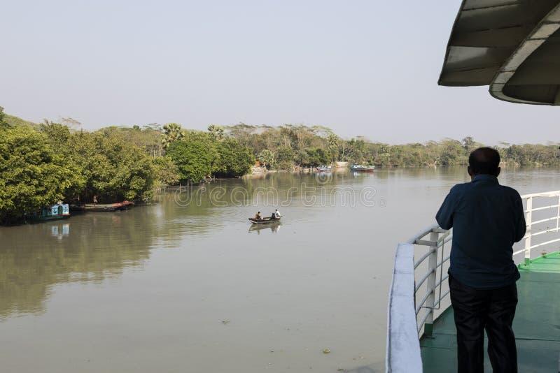 Khulna, Bangladesh, il 1° marzo 2017: L'uomo sta all'arco di un traghetto immagini stock libere da diritti