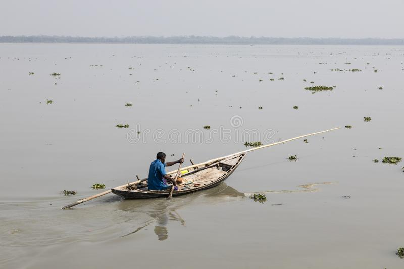 Khulna, Bangladesh, March 1 2017: Man rowing with a small wooden boat on a river near Khulna. In Bangladesh royalty free stock photography