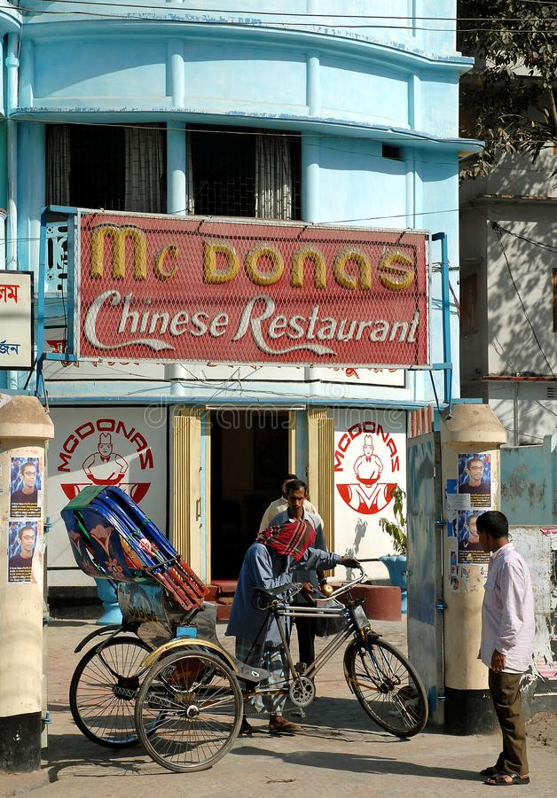 Khulna, Bangladesh: Mc Dona`s Chinese Restaurant in Khulna, an unapologetic rip-off of McDonalds. A rickshaw driver is outside. Local life scene in Khulna stock images