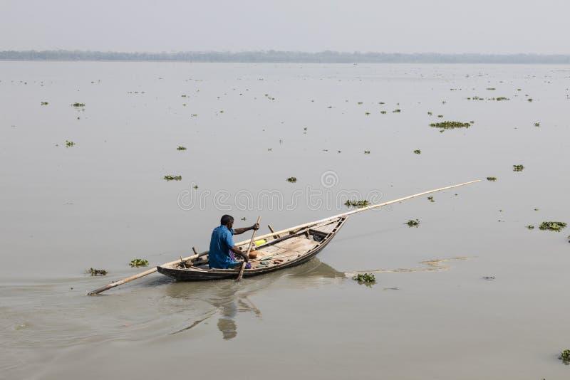 Khulna, Bangladesh, o 1º de março de 2017: Enfileiramento do homem com um barco de madeira pequeno em um rio perto de Khulna fotografia de stock royalty free