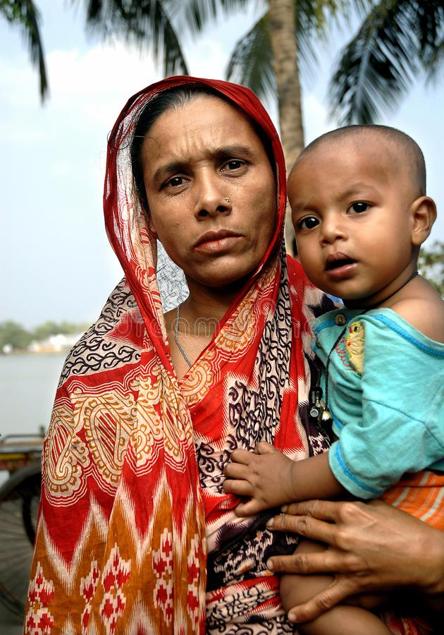 Khulna, Bangladesh: Woman in traditional clothes holding a baby. Local life in Khulna, Bangladesh stock images