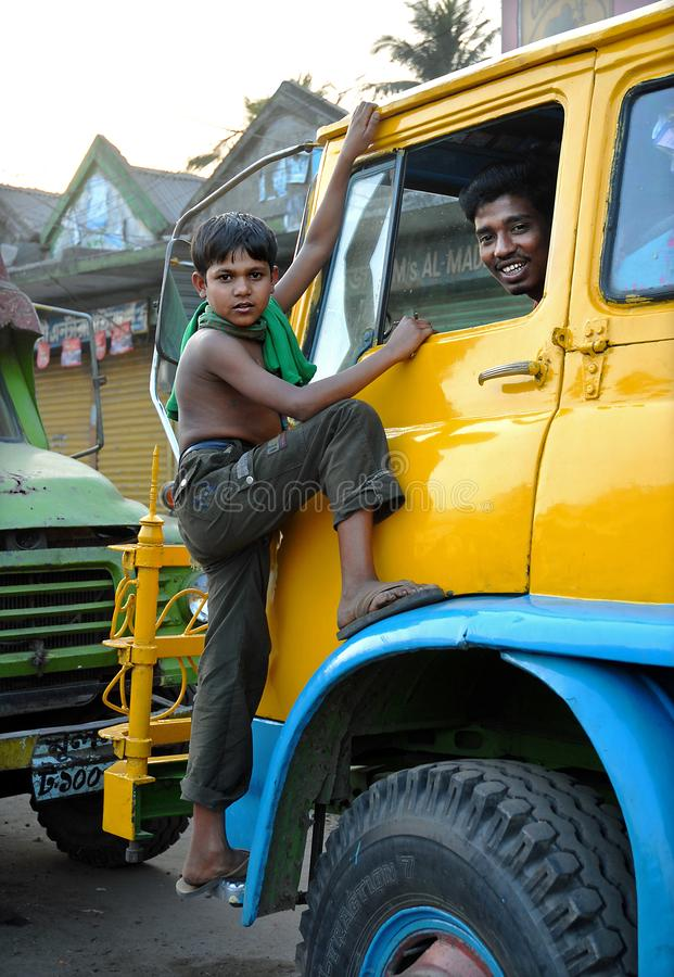 Khulna, Bangladesh: A young boy climbs on the cab of a truck in Khulna with the smiling driver inside. Charming local life scene in Khulna, Bangladesh stock images
