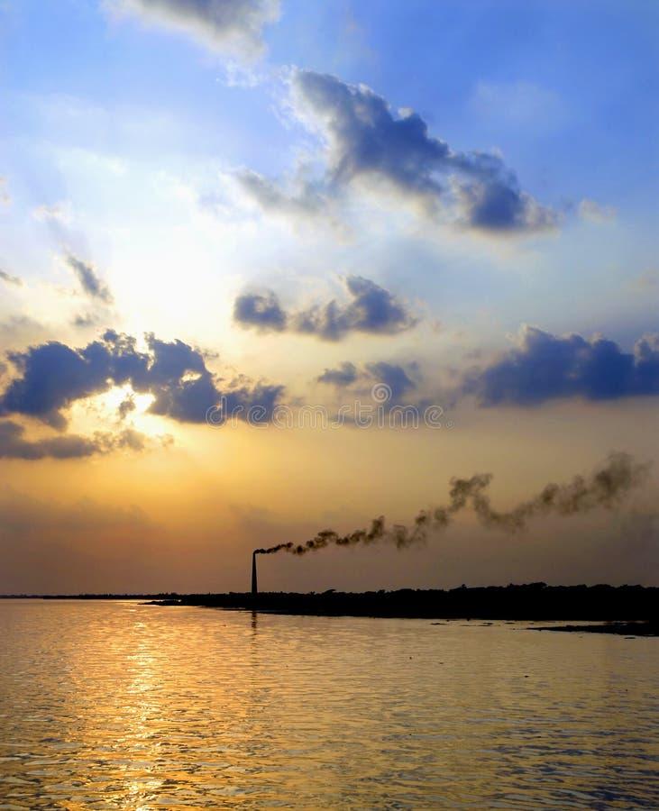 Khulna, Bangladesz: Zachód słońca nad rzeką Rupsa koło Chulny z zanieczyszczającym stosem dymnym zdjęcie stock